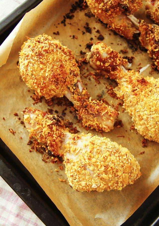 Gambe di pollo fritto in pentola nera con carta avvolta immagine stock