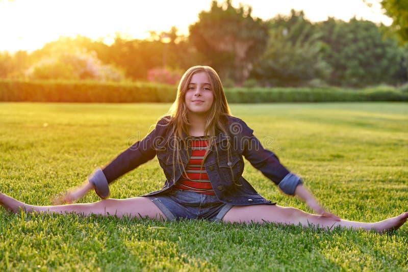 Gambe di scissione della ragazza bionda del bambino al parco di tramonto immagini stock libere da diritti