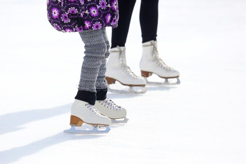 Gambe di un adulto e di un bambino che pattinano sulla pista di pattinaggio sul ghiaccio fotografia stock