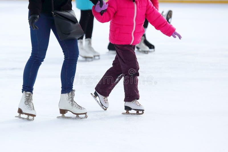 Gambe di un adulto e di un bambino che pattinano sulla pista di pattinaggio sul ghiaccio fotografie stock