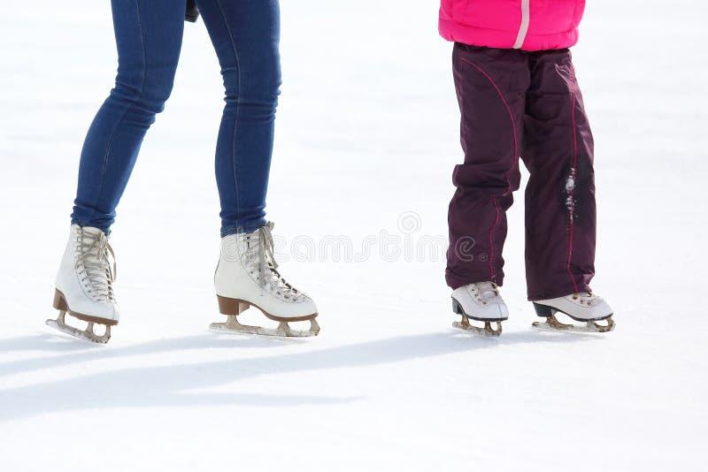 Gambe di un adulto e di un bambino che pattinano sulla pista di pattinaggio sul ghiaccio fotografia stock libera da diritti