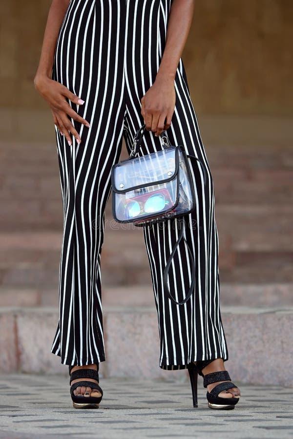 Gambe di una donna alla moda vestita immagine stock