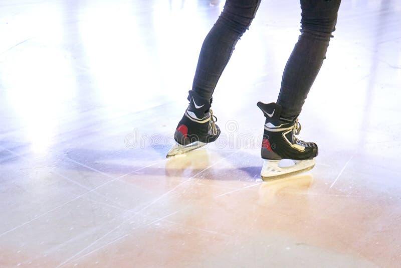 Gambe di una donna che pattina su una pista di pattinaggio sul ghiaccio immagine stock