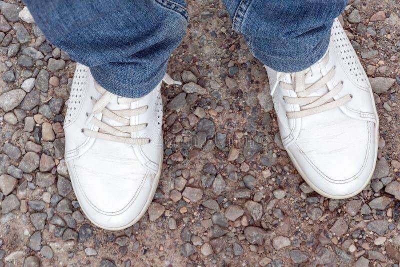 Gambe di una persona in jeans e scarpe da tennis bianche Vada via la strada fotografia stock libera da diritti