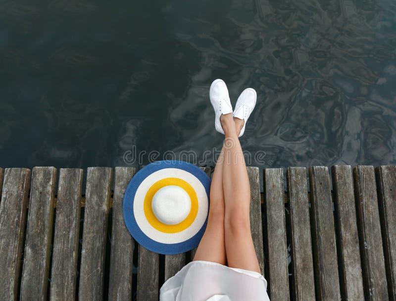 Gambe di una ragazza caucasica sulla spiaggia con un primo piano del cappello della spiaggia immagine stock