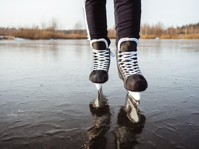 Gambe di una ragazza su pattini da hockey sul ghiaccio di un lago Sullo sfondo di una foresta fotografie stock