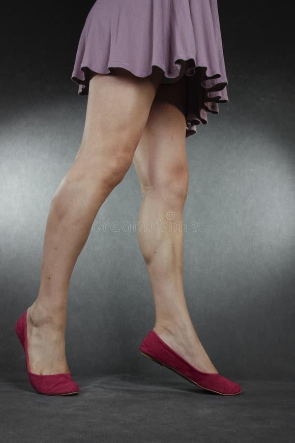 Gambe e piedi della donna che indossano vestito e le scarpe porpora sopra il BAC grigio fotografia stock