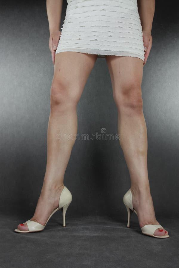 Gambe e piedi della donna che indossano vestito ed i talloni sopra il backgrou grigio fotografia stock libera da diritti