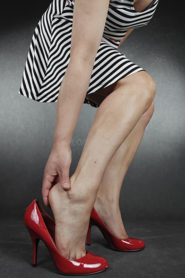 Gambe e piedi della donna che portano vestito che mette sulle scarpe fotografia stock libera da diritti