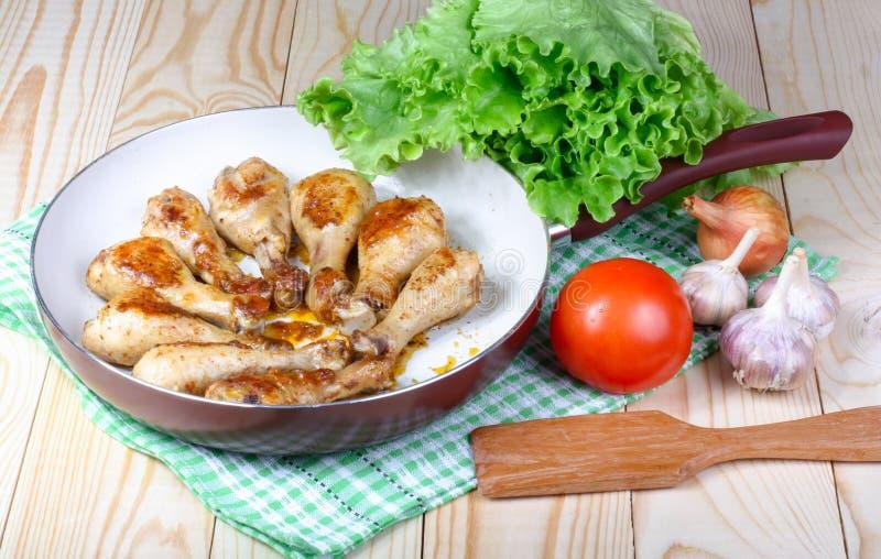 Gambe e verdure di pollo fritto del pranzo sulla tavola di legno fotografie stock