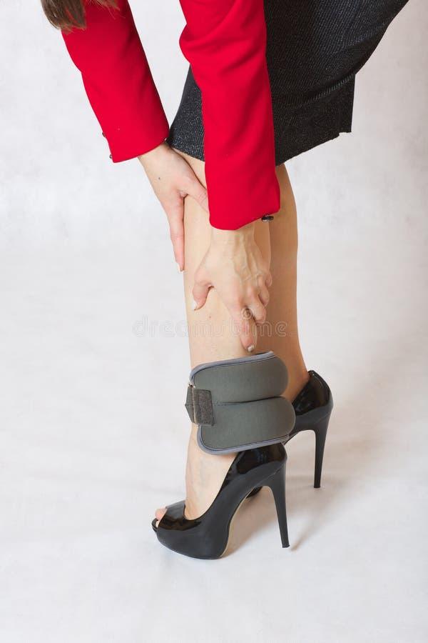 Gambe esili con il peso della sabbia della caviglia sui tacchi alti immagine stock