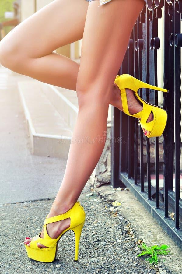 Gambe esili lunghe sexy della donna in scarpe gialle esterno immagine stock