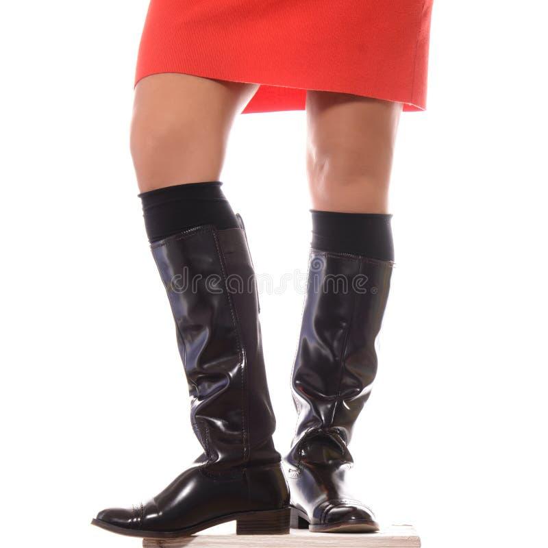 Gambe femminili in alti stivali di cuoio marroni isolati su bianco fotografie stock