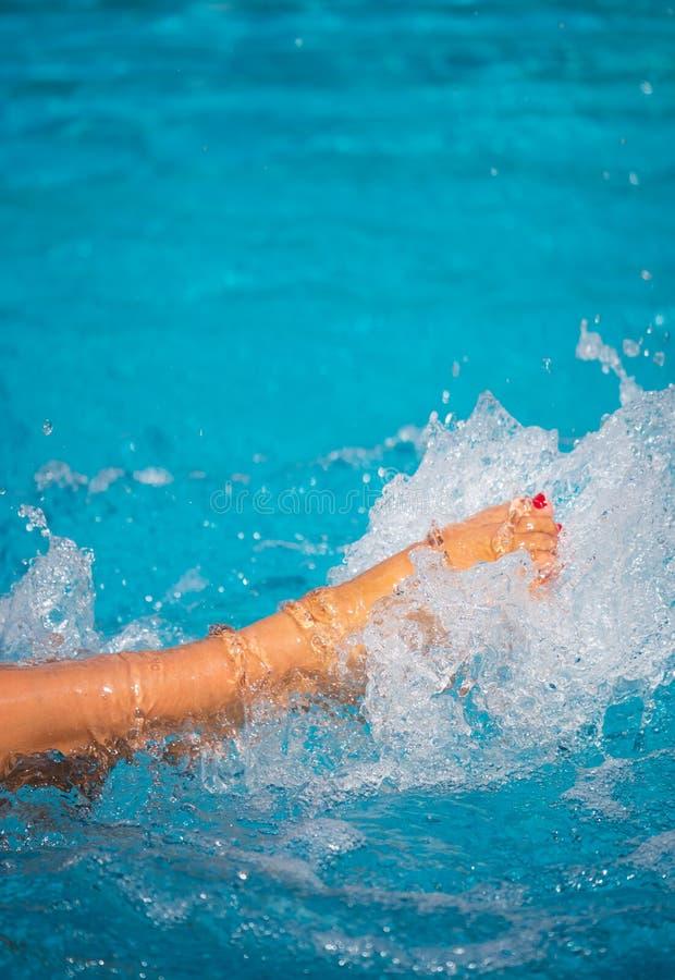 Gambe femminili che spruzzano acqua allo stagno immagini stock libere da diritti