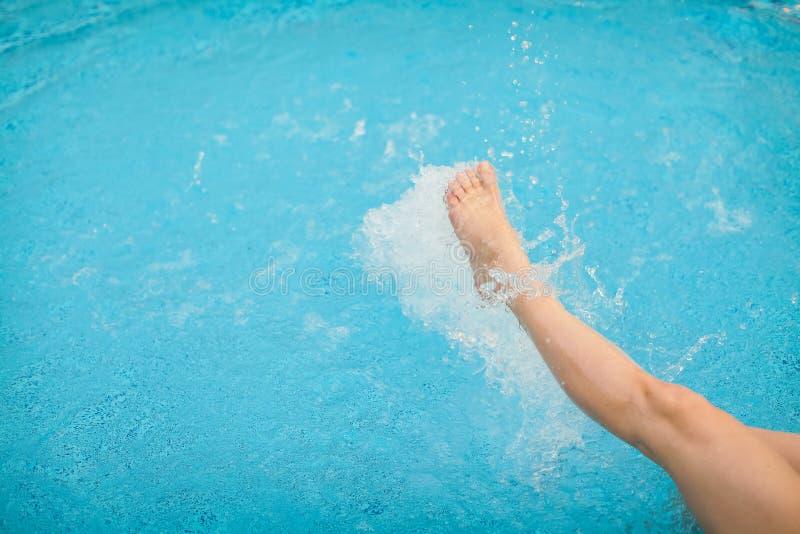 Gambe femminili che spruzzano acqua nella piscina blu, fuoco selettivo fotografia stock libera da diritti