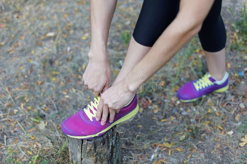 Gambe femminili Donna in scarpe da tennis lilla luminose dei legami neri degli abiti sportivi con i laccetti della calce, prepara immagine stock