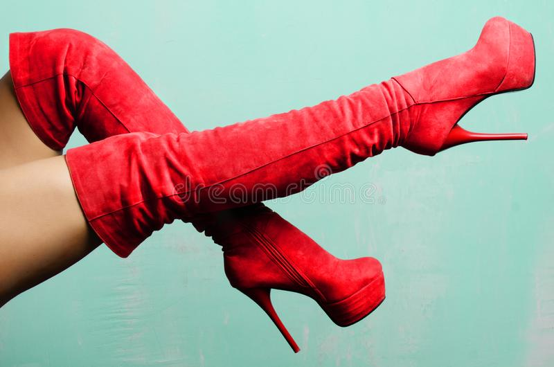 Gambe femminili negli stivali a tacco alto della pelle scamosciata rossa immagine stock