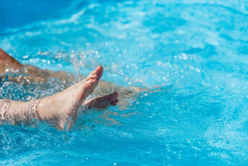Gambe femminili nell'acqua nello stagno, primo piano immagine stock
