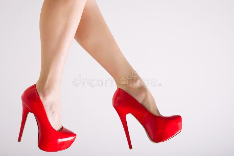 Gambe femminili perfette che indossano i tacchi alti rossi su fondo bianco fotografia stock