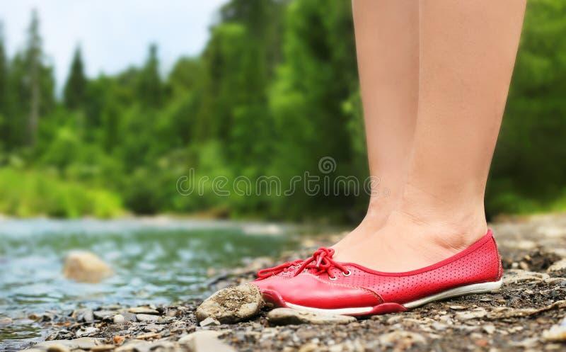Gambe femminili in scarpe rosse su un fondo di paesaggio fotografie stock