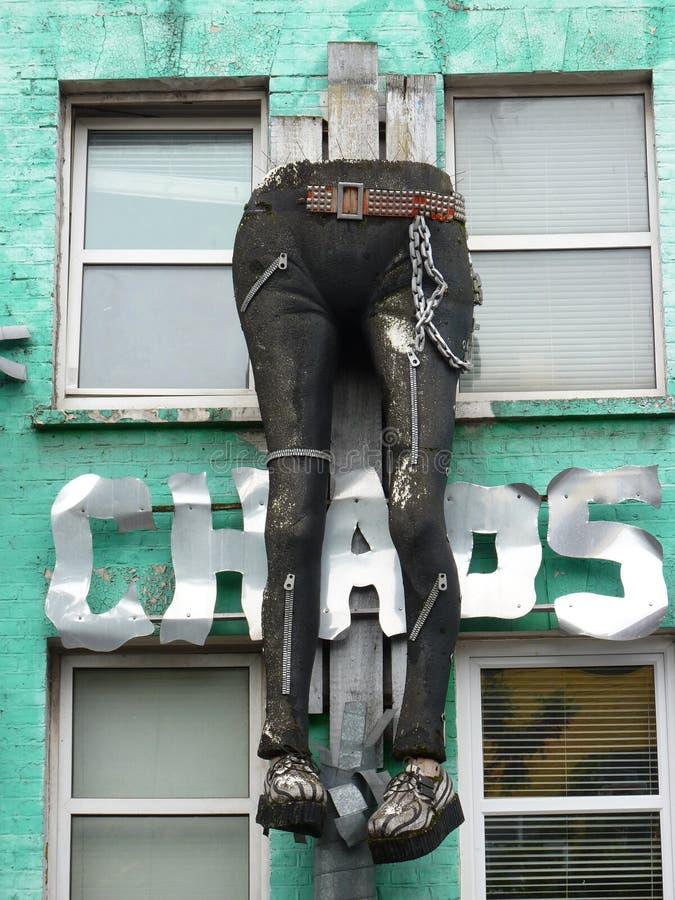 Gambe in jeans che appendono giù una parete fotografia stock