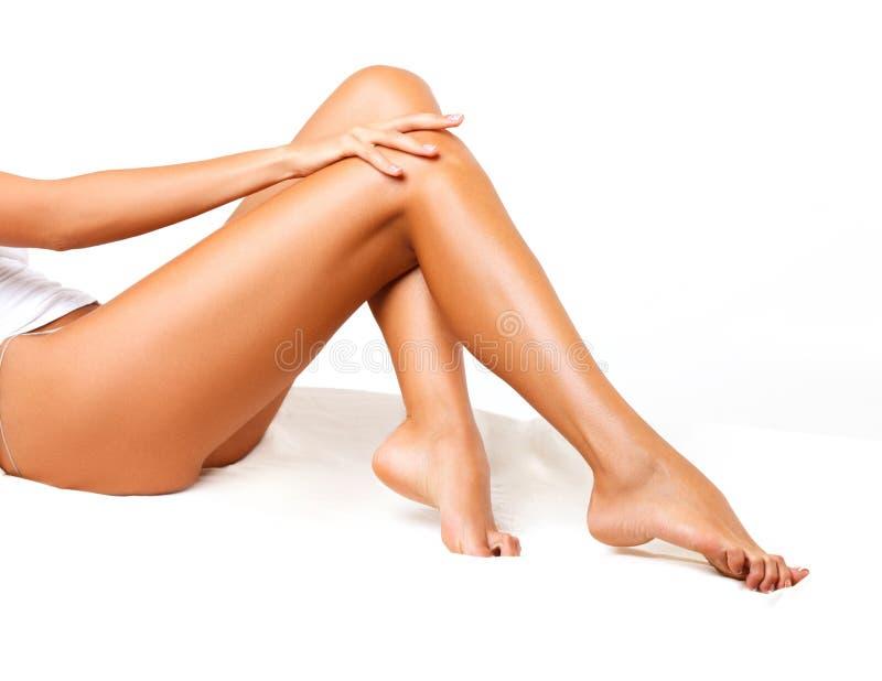 Gambe lunghe della donna isolate su bianco. immagine stock