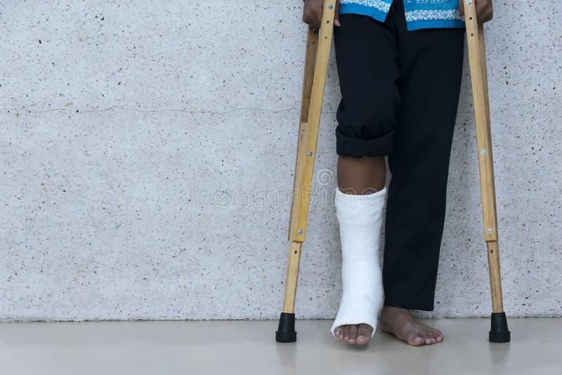 Gambe rotte e grucce di uso come supporto da camminare fotografia stock libera da diritti