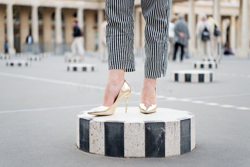 Gambe in scarpe dorate Parigi, Francia di fascino Scarpe del tacco alto sui piedi femminili sul quadrato di citt? Scarpe di modo  fotografia stock