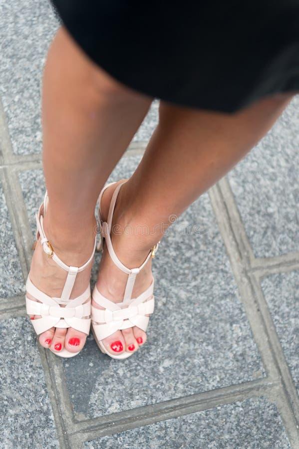 Gambe in scarpe sexy sui tacchi alti a Parigi, Francia Piedi di pedicure della femmina su pavimentazione grigia Modo, bellezza, s fotografie stock