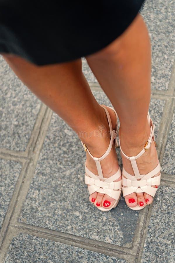 Gambe in scarpe sexy sui tacchi alti a Parigi, Francia Piedi di pedicure della femmina su pavimentazione grigia Modo, bellezza, s fotografia stock libera da diritti