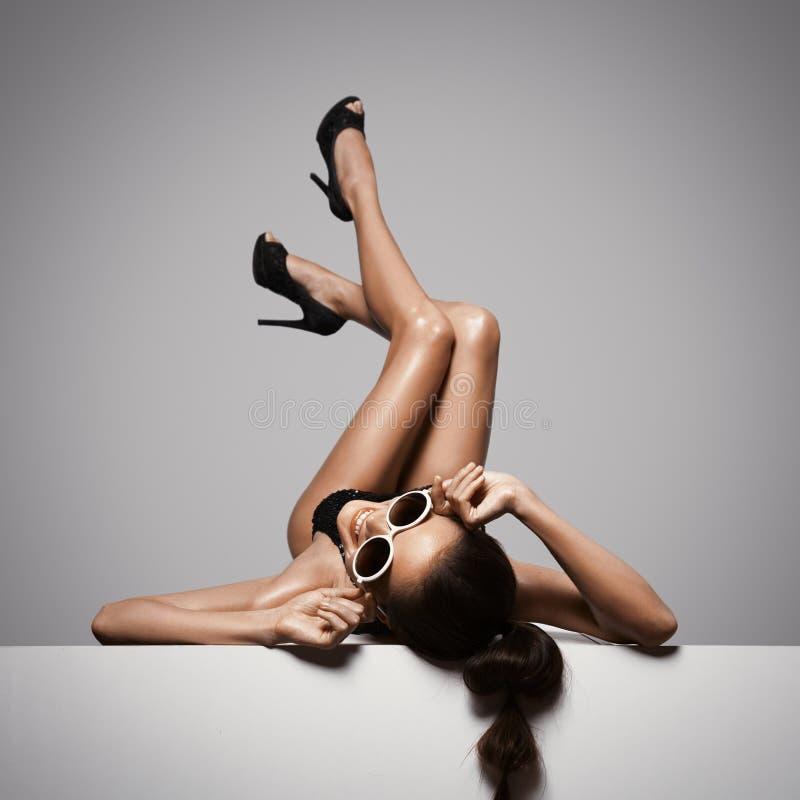 Gambe sexy della donna in scarpe nere Fondo grigio fotografia stock libera da diritti