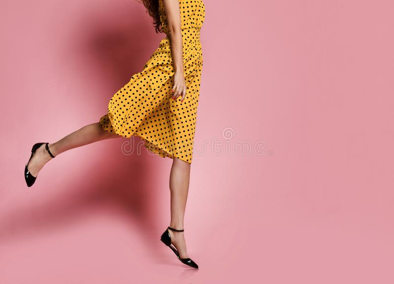 Gambe snelle femminili in scarpe eleganti ed in una barca ed in un vestito da estate con i pois in un salto su un fondo rosa immagine stock
