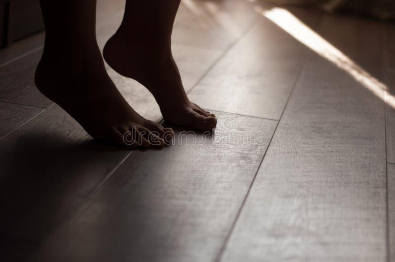 Gambe su un pavimento di legno caldo immagine stock