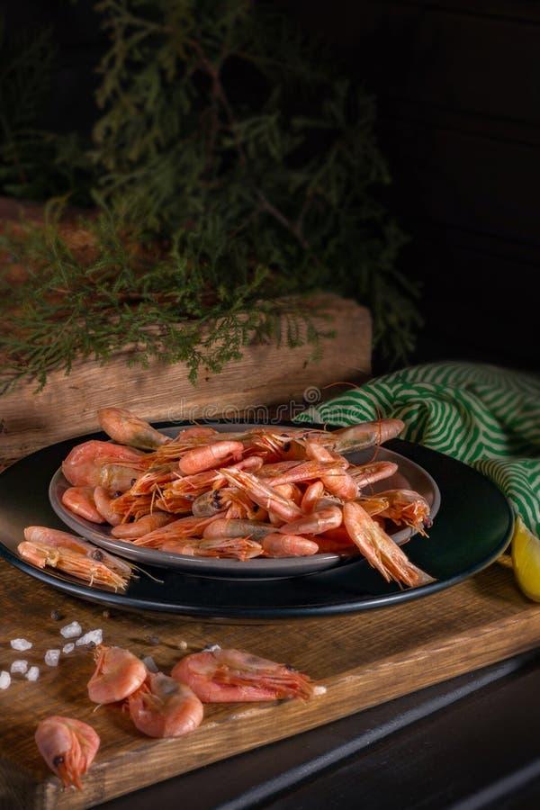 Gamberetti appetitosi su una tavola di legno Vicino al vecchi ceppo e cipresso fotografie stock
