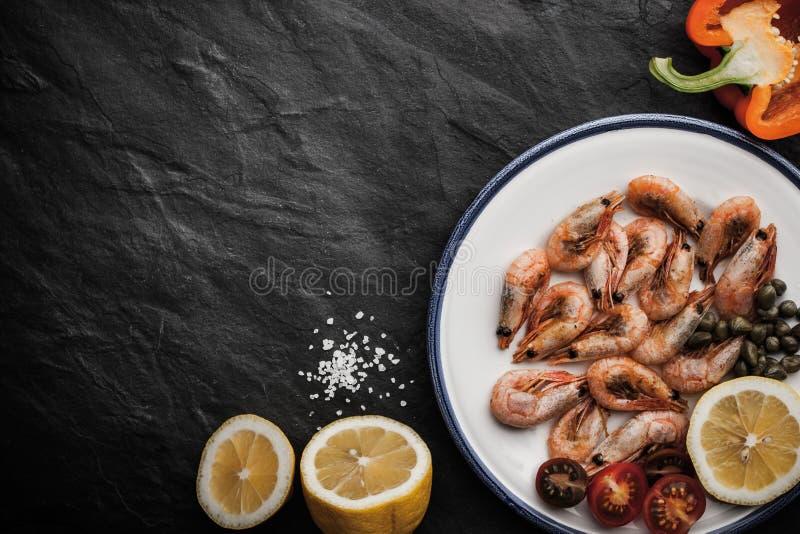 Gamberetti arrostiti con il limone e le verdure sul piatto ceramico sulla tavola di pietra nera immagine stock libera da diritti