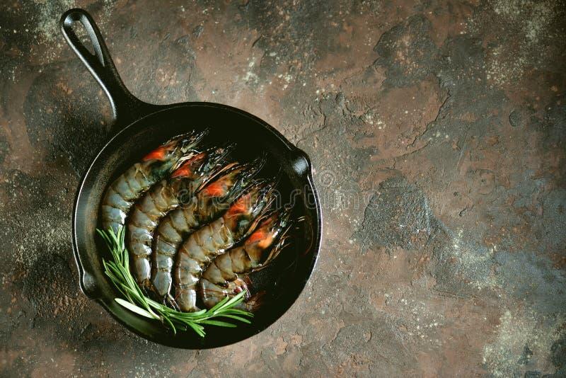 Gamberetti freschi crudi della tigre con una padella della ghisa con il sale fresco di rosa e dei rosmarini Frutti di mare sani fotografia stock