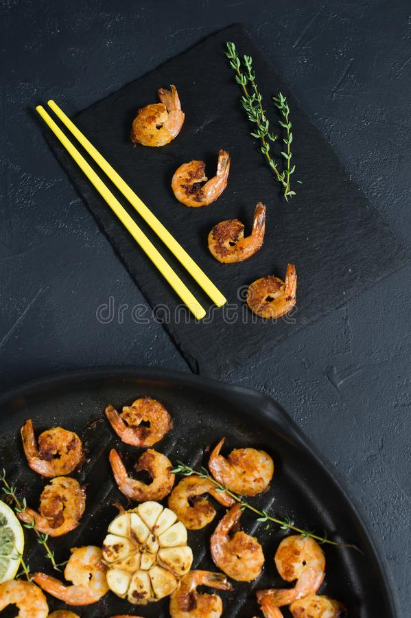 Gamberetti fritti di re in una padella su un fondo nero con i bastoncini gialli fotografia stock libera da diritti