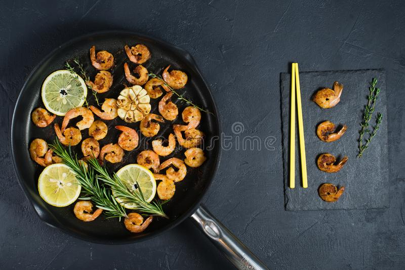 Gamberetti fritti di re in una padella su un fondo nero con i bastoncini gialli fotografie stock libere da diritti