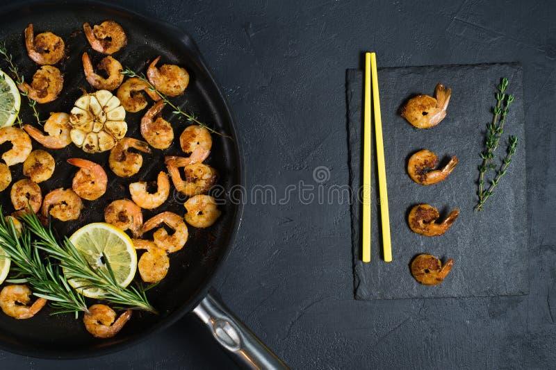 Gamberetti fritti di re in una padella su un fondo nero con i bastoncini gialli immagini stock