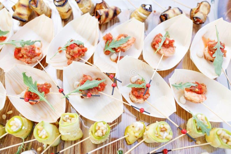 Gamberetto delizioso e pomodori affettati su una barca di legno Lo zucchini rotola con i pinoli Tavola di buffet saporita Partito immagini stock