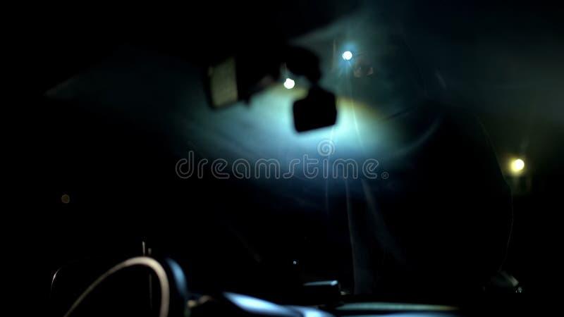 Gamberro en salón illuminating del coche de la mascarilla con la linterna antes del robo imagen de archivo libre de regalías
