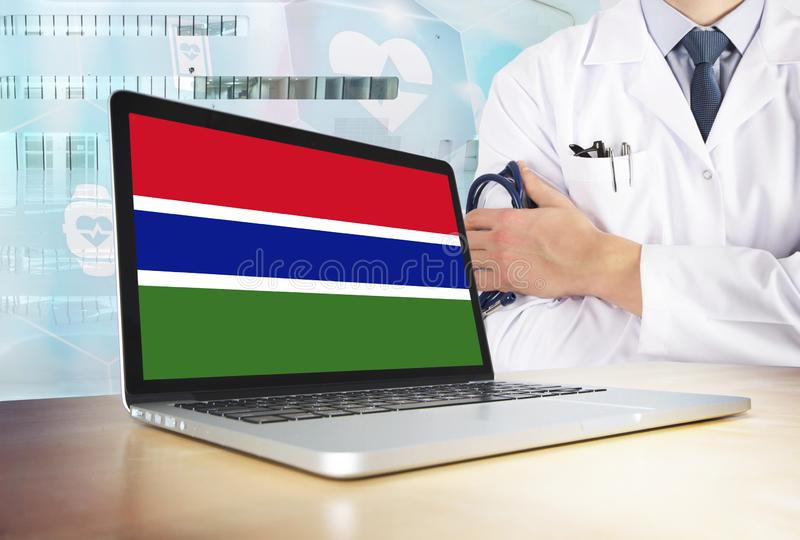 Gambia healthcare system in tech theme. Gambian flag on computer screen. Doctor standing with stethoscope in hospital. Cryptocurrency and Blockchain concept stock photo