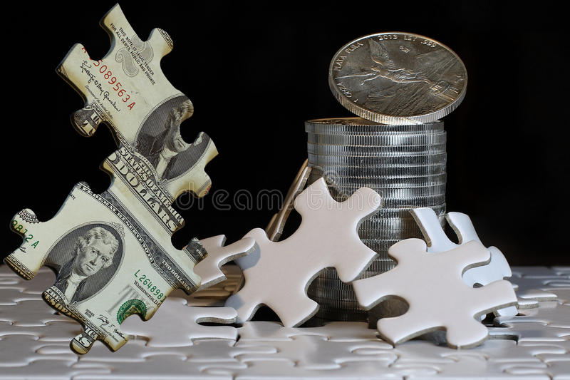 The gamble of hard assets going through the financial puzzle. Financial concept background made of hard assets going through the financial puzzle royalty free stock photography