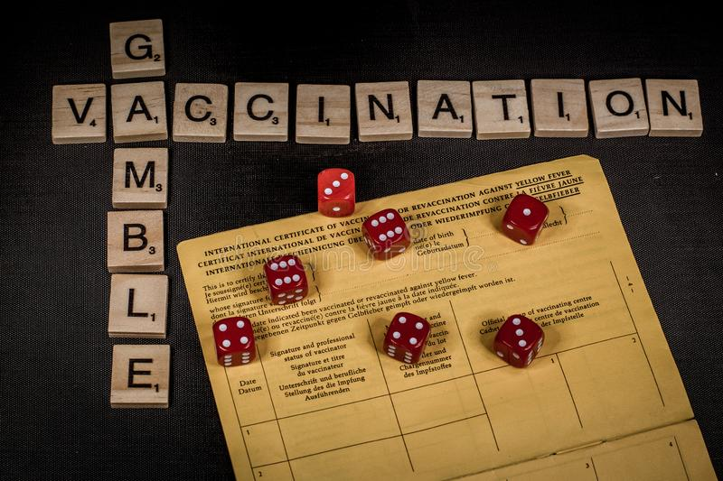 The gamble with vaccination. Gambling your health by not getting vaccination shots versus immunity with the words vaccination andd gamble spelled out in scrabble stock photos