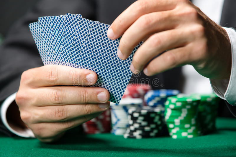 Gambler playing poker cards with chips on the poker table. Gambler playing poker cards with poker chips on the table. Risky entertainment of gambling stock image