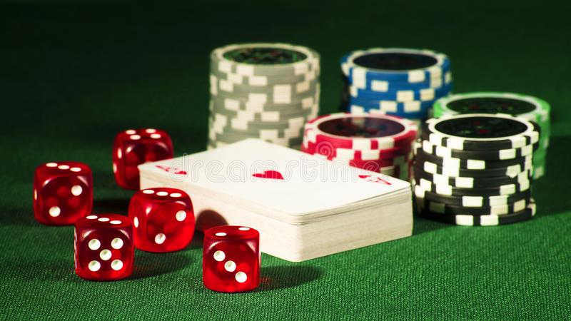 Gambling concept - cards, bones and chips on a green gown stock images