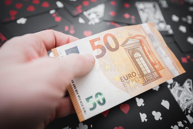 gambling 50 Euros em uma mão acima do fundo preto dos cartões de jogo foto de stock