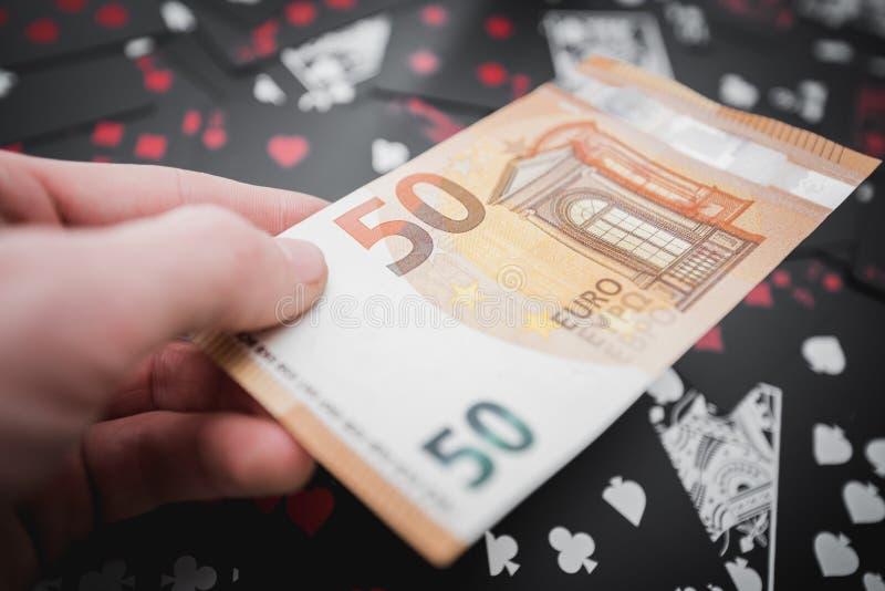 gambling 50 Euros em uma mão acima do fundo preto dos cartões de jogo fotos de stock