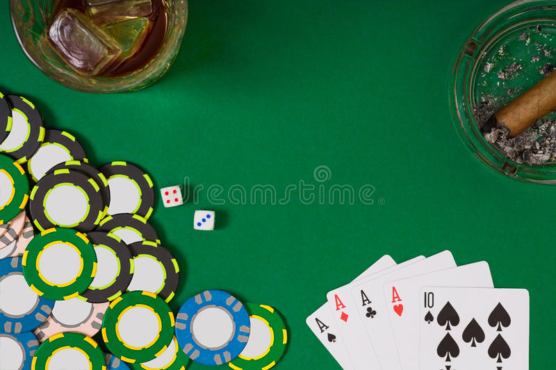 Gambling, fortune and entertainment concept - close up of casino chips, whisky glass, playing cards and cigar on green. Table surface. Top view. Still life royalty free stock photography