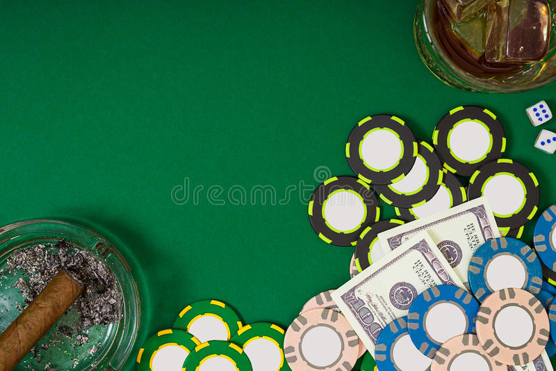 Gambling, fortune and entertainment concept - close up of casino chips, whisky glass, playing cards and cigar on green. Table surface. Top view. Still life stock image